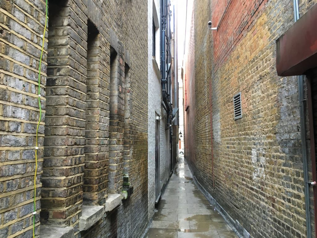 Very thin alley in London with red brick, yellow brick and brown brick walls