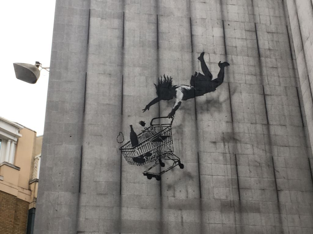 Banksy mural of a shopper and trolley falling from height