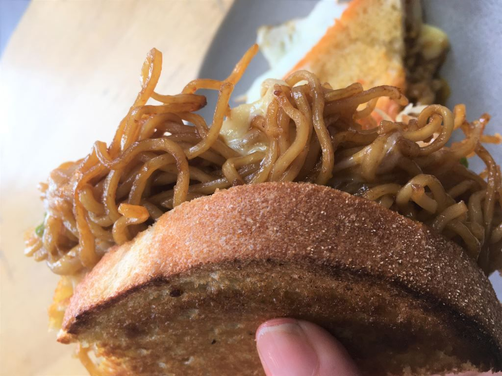 toasted sandwich with noodles hanging out of the side