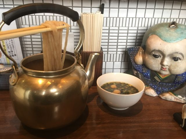 Zubora Udon in Fukuoka. Picture shows the kettle the noodles are cooked in. A pair of chopsticks are holding noodles coming out of it and a bowl of dipping sauce with green chillis floating on the top.