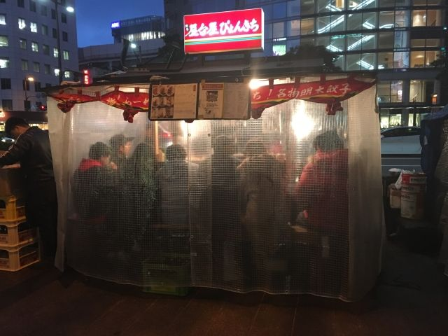 Dining at a Yatai is a one of things to do in Fukuoka. The image shows a yatai, a small outdoor stall covered in plastic. Inside is a bar with about 7 customer sat inside having a drink.