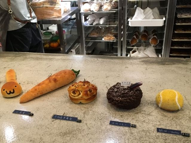 Cute cakes and breads from Just In Bakery Taipei. There is a bread shaped like a worn, bread shaped like a carrot, an apple cake, a chocolate cake and then a stollen shaped like a tennis ball.