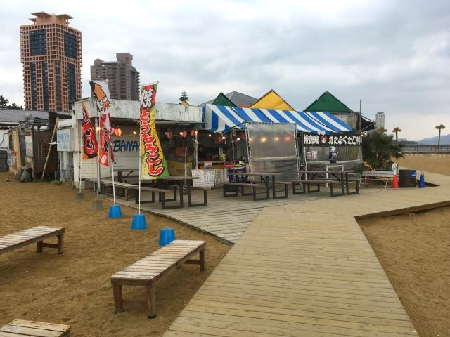 The boardwalk in Fukuoka has small beach shacks with blue and white stripy awnings and benches outside.