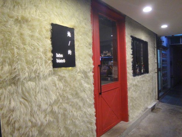 Hers Bistro cute cafe in Taipei. It has a black sign reading hers bistro. A bright red door and walls covered in white fun fur.