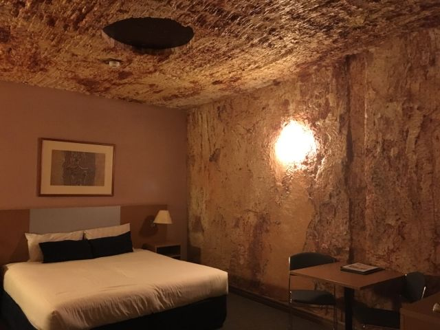 An underground room at the Desert Cave Hotel, Coober Pedy, It has square rock walls that have been dug into the cliff. They are red and white due to the different rocks in the cliffs.