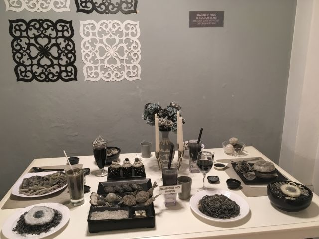 Image of food on a table. It looks like it has been taken in black and white, but it's not - instead the food is all plastic models in black and white.
