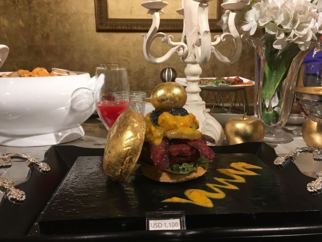 Table of plastic models of the world's most expensive food. This shows a US$1100 dollar topped with a gold leaf covered bun