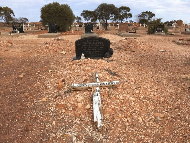 Grave covered in stones with a white cross on top. The headstone is black marble and has two statues of cats.