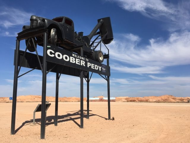 The Welcome to Coober Pedy sign. It's a black mining truck on the top of six poles with a sign saying 'Welcome to Coober Pedy'