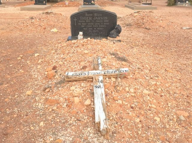 Image of grave with two cat staues and a simple white cross