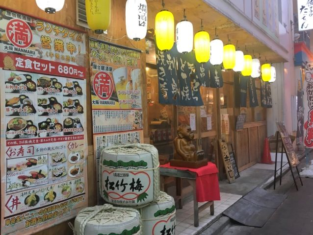 Restaurant in Kokura Japan lit up for night trade. A row of yellow and white lanterns glows outside the door.