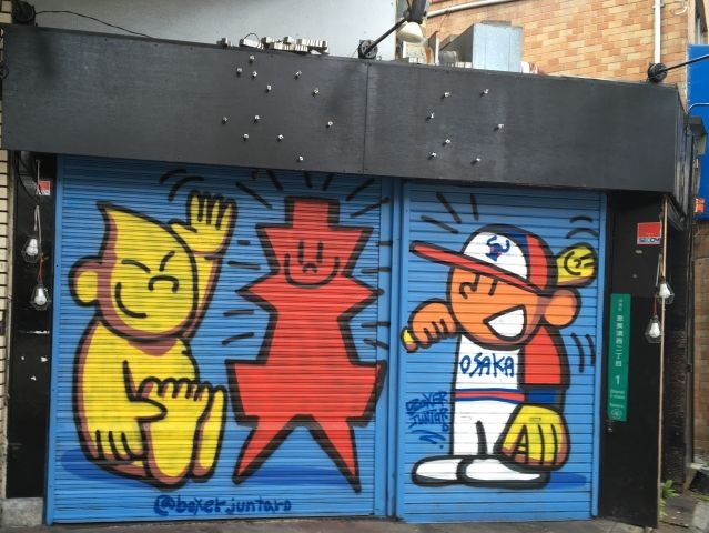 painted street art on a shutter in Osaka containing a yellow Billiken