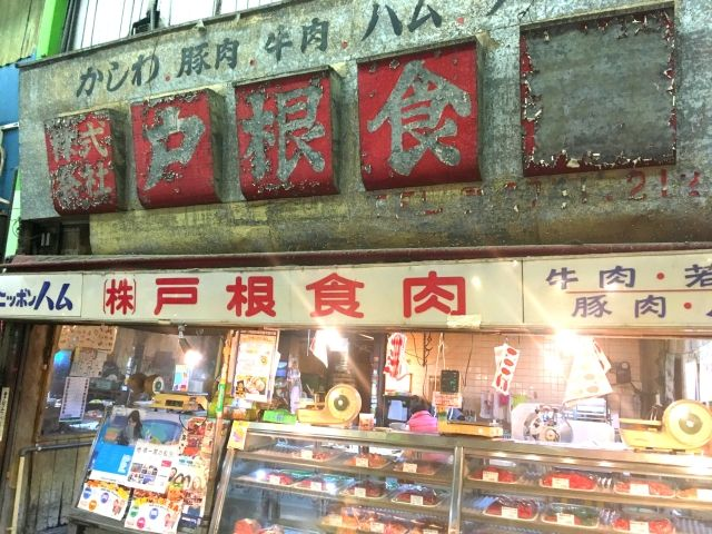 Market stall in Kokura Tanga market, selling meat with a red faded sign containingJapanese writing