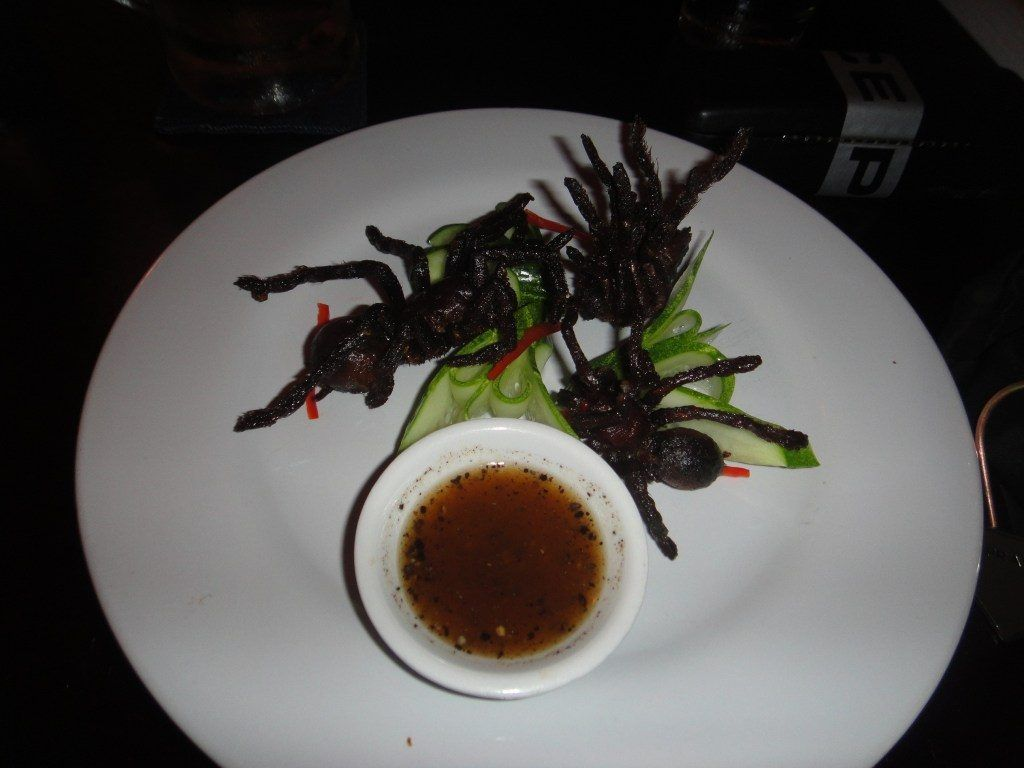 White plate containing three deep fried tarantulas with a bowl of dip