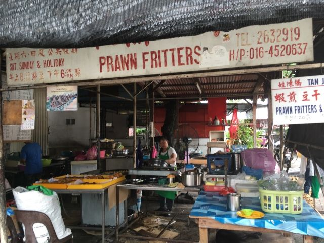 Shop selling prawn fritters in Penang with the chef at her fryer