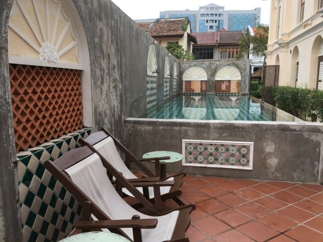 Pool with two deckchairs next to at Jawi Perakanan, Penang