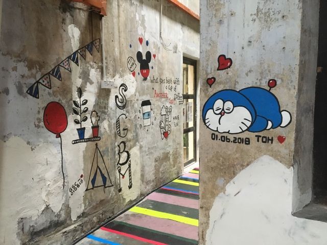 Alley full of paintings of cartoon cats and rainbow steps