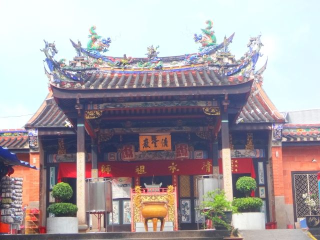 Temple with red walls and an ornate carved roof