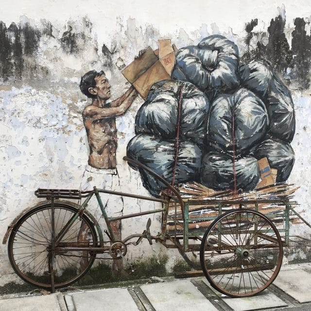 mural of a man piling garbage bag onto a bicylce - using a real bicycle as part of the art