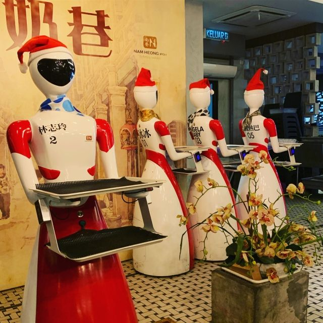 Four fobot waitresses with trays in Ipoh Malaysia