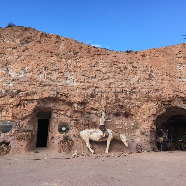 Two doors in a cave with a horse statue outside at Crocodile Harry's House, Coober Pedy