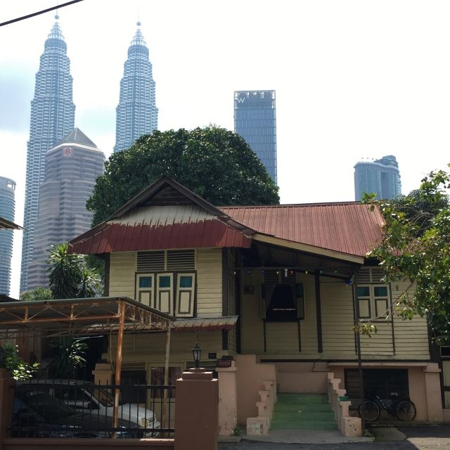 View of Kuala Lumpur's Petronas Towers over an old house in Kampung Baru