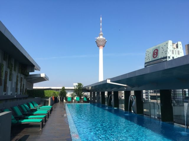 Long thin swimming pool with a view of the KL Tower