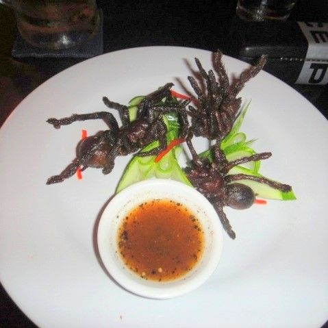 Three fried spiders on a plate at Romdeng, Cambodia
