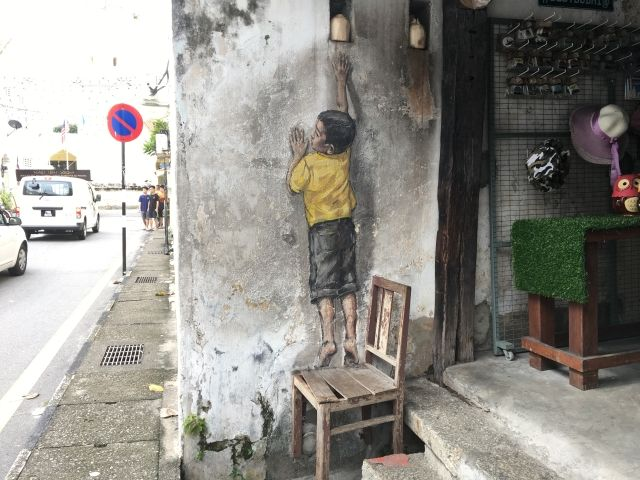 Art work of a boy climbing on a chair - the boy is painted, the chair is real