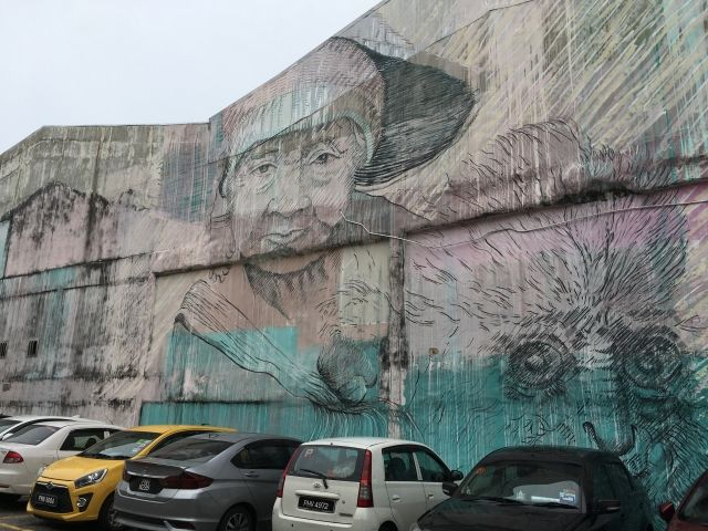 Pastel coloured mural of a woman with a monkey in Penang