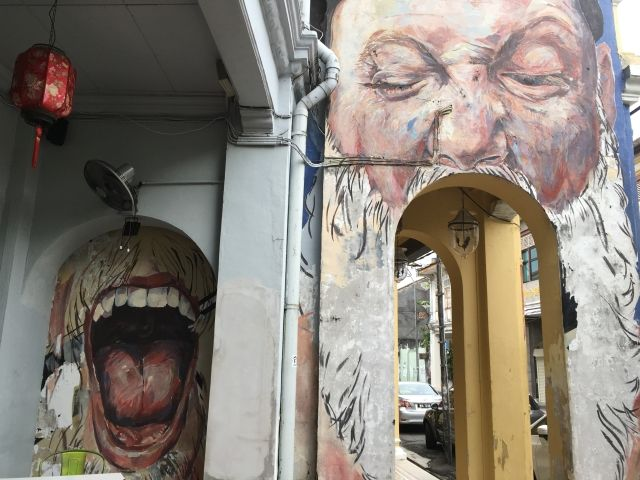 Street art mural of a face, the mouth is painting next door - but an arch under the painting forms a mouth