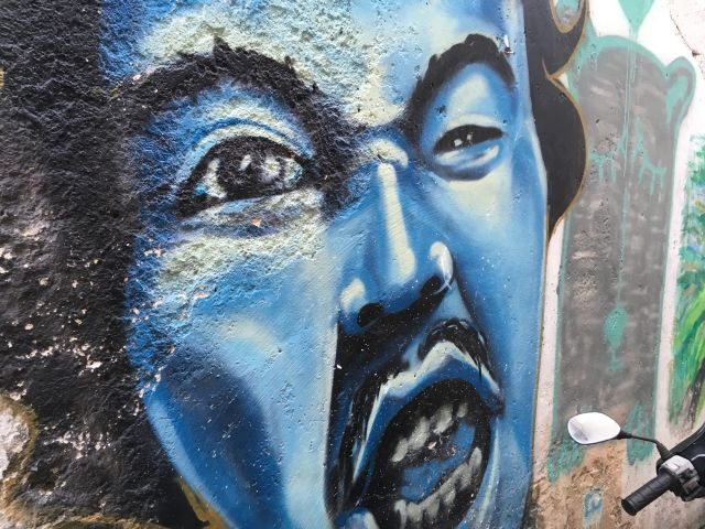 Close up mural of a man with a blue face grimacing