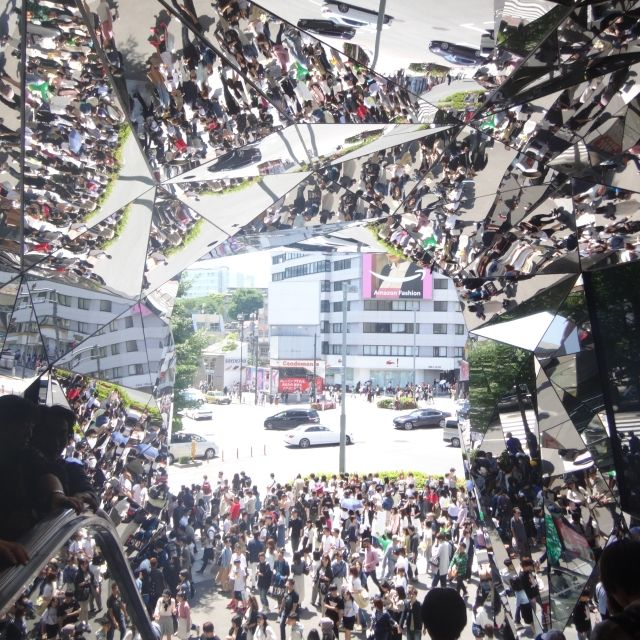 Mirrored shop front creating image of a crowd in Tokyo during Golden Week