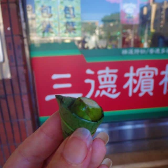 Hand holding a small green betel nut outside a betel nut seller in Taipei, Taiwan