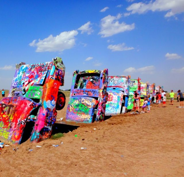 Row of brightly coloured cars stuck in the ground at Cadillac Ranch near Amarillo, Texas