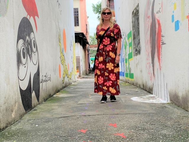 Woman standing in alley with murals in Klang, Malaysia