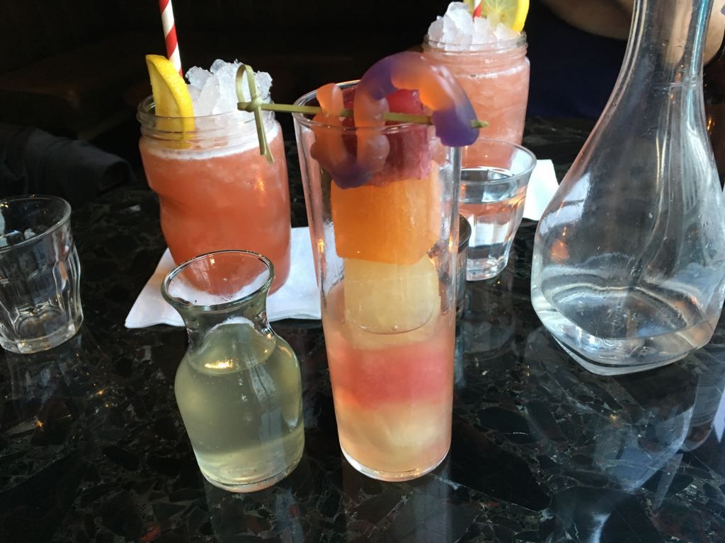 Cocktail with coloured bands of liquid and a jelly snake