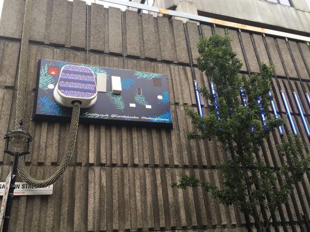 Giant Plug artwork on a wall in Soho London
