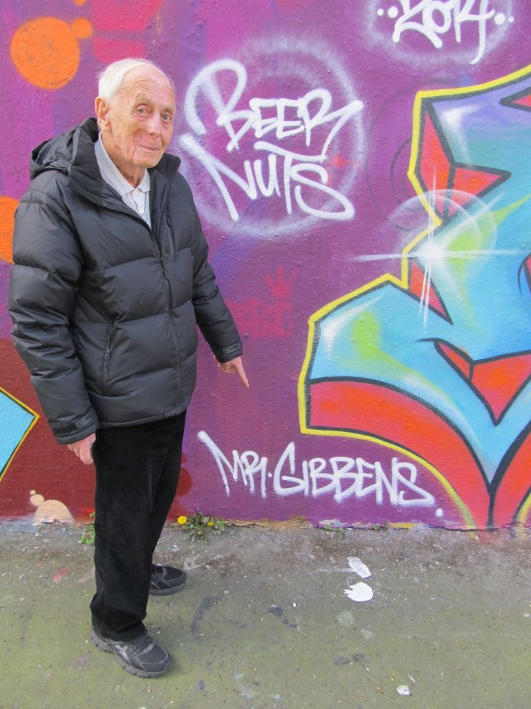 Street art photographer Gordon Gibbens standing by a mural