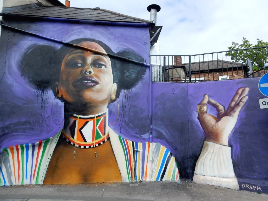 Mural of black woman with her hair in two buns and a choker round her neck by artist Dreph