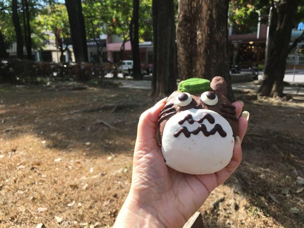 Hand holding a cake shaped like Totoro