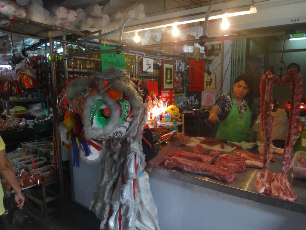 Man in Lion Dance costume stands near meat stall in Thewet Market, by Khao San Road