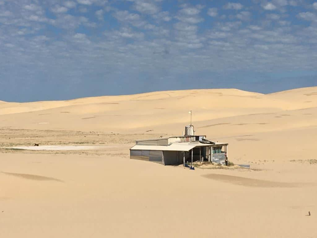 a tin shack surrounded by sand dunes
