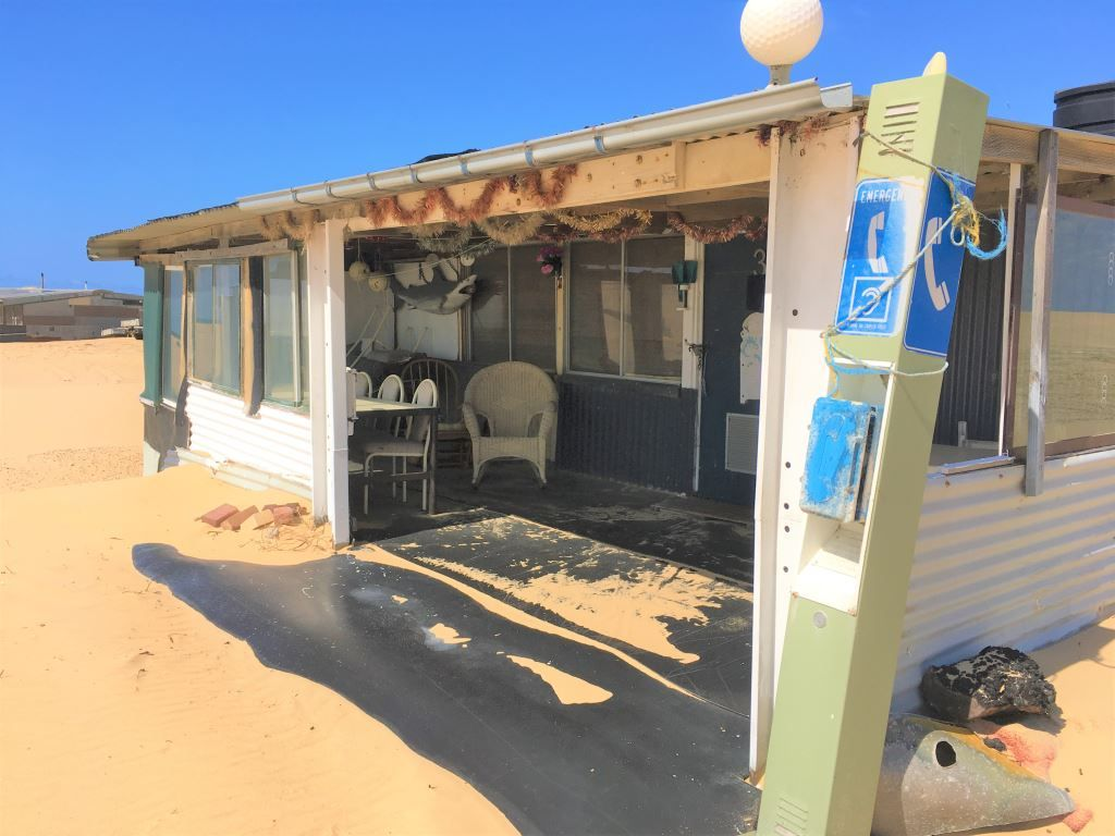 ton shack decorated with a pay phone and plastic shark in Tin City near port Stephens