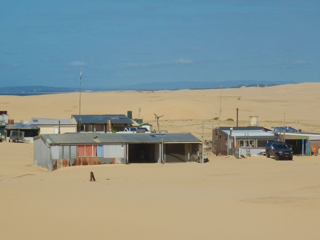 tin chack homes surrounded by sand dunes at tin city stockton