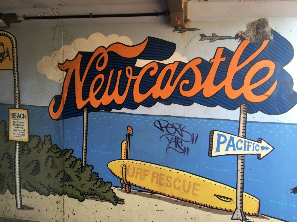 Painted mural saying Newcastle in orange cursive font in Newcastle NSW