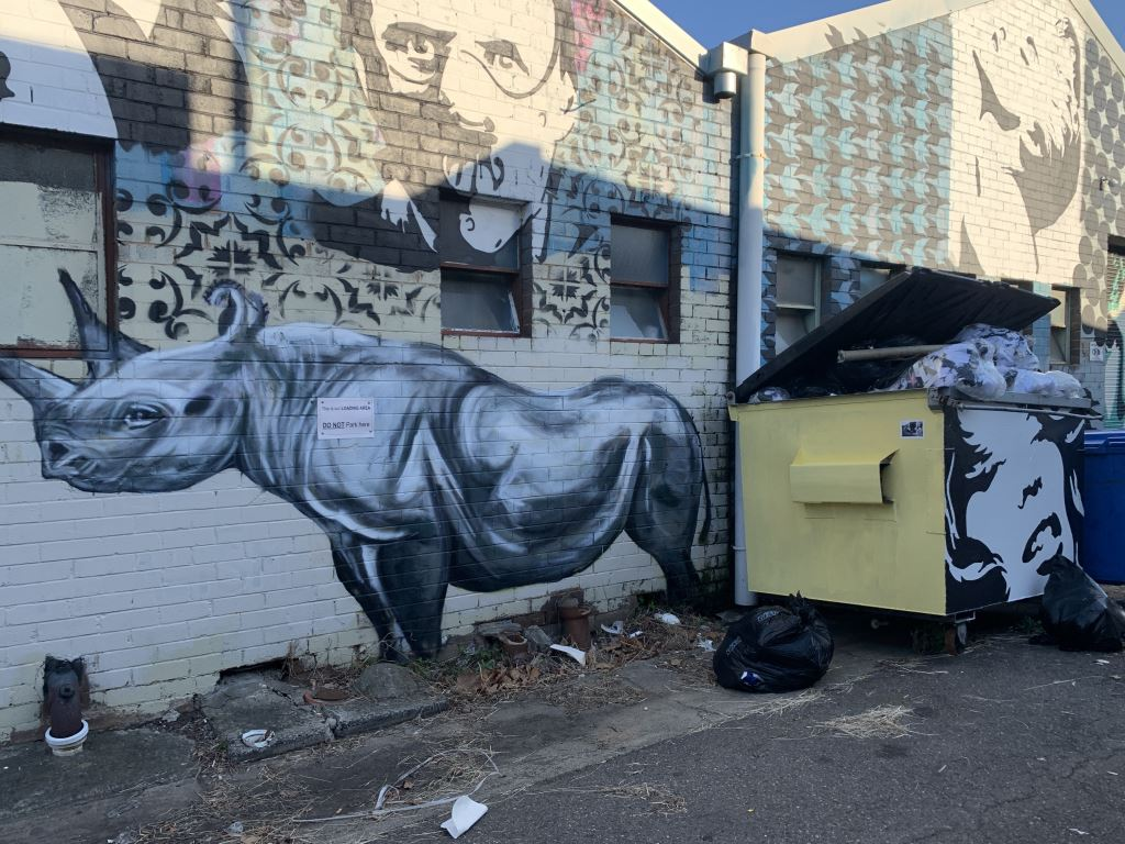 mural of a rhino with another image of Hannibel Lecter behind.