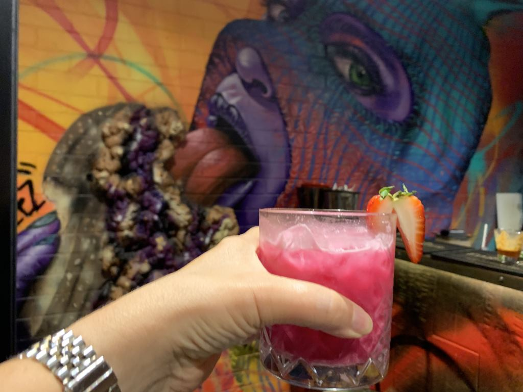 red cocktail being held up in front a street art mural in Peanut Butter Jelly Bar, Manly