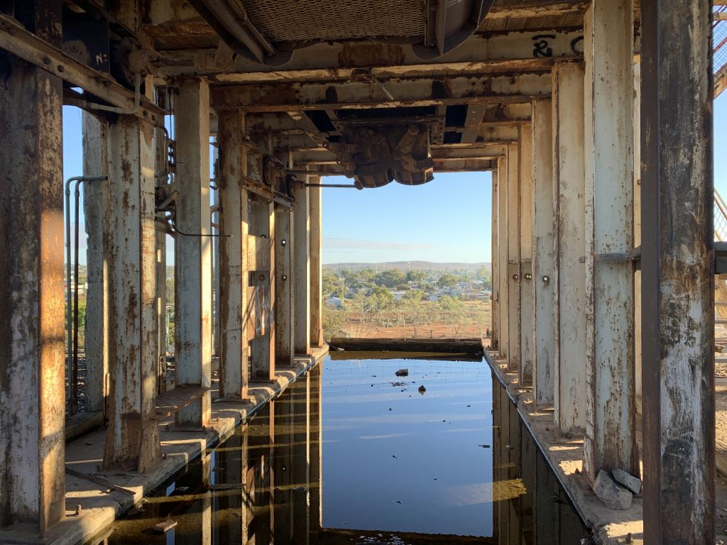 metal struts in an old mine over a puddle - a view of Broken Hill is in the distance
