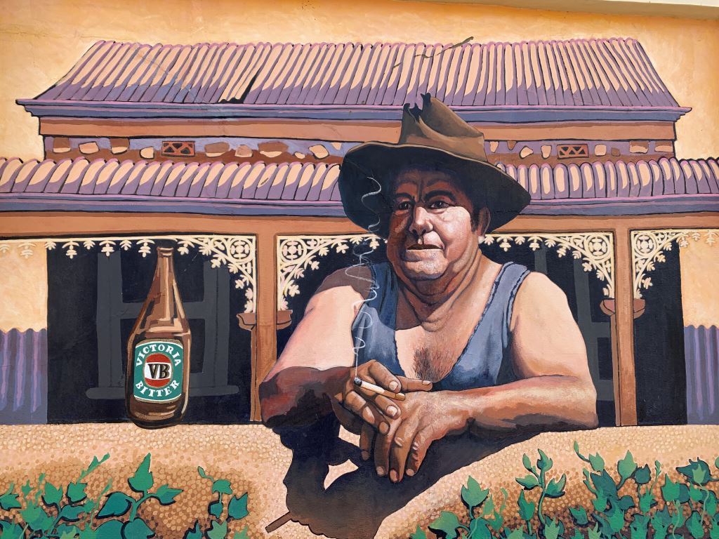 mural of an Australian man in a singlet and hat outside a pub holding a VB